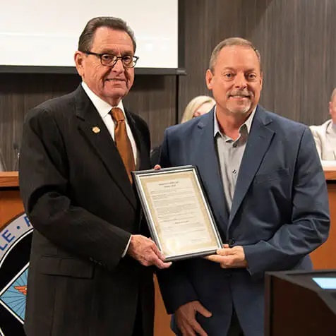 Mayor Harold Perrin (left) presents Bob West with a proclamation recognizing Hytrol's contributions during Manufacturing Day 2018.