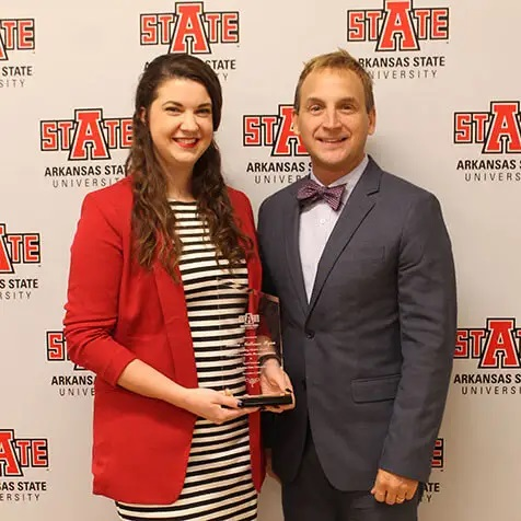 Associate Dean Lance Bryant (right) presents Lauren Matheson Ryan with the 2018 Outstanding Alumni Award from the Arkansas State University Department of Health, Physical Education and Sport Sciences.