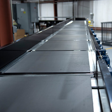 Belted conveyor that provides gaps between products.